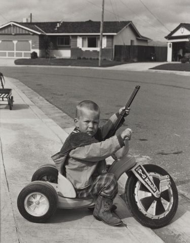 """""""Untitled (Richie with Gun)"""" (1971) Bill Owens, gelatin silver print. Collection of the Art Fund, Inc. at the Birmingham Museum of Art; Gift of the Jack and Rebecca Drake Collection, AFI.106.2015"""