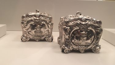 """This pair of tea canisters is an example of Godfrey's skill as silversmith, though she was also a renowned goldsmith. Her first husband, Abraham Buteux, was a goldsmith from the French immigrant community, and she carried on his business after his death until she remarried in 1732 to Benjamin Godfrey. After his death, she registered for her second mark (used by smiths to """"sign"""" a piece) under the name of Elizabeth Godfrey in 1741. Godfrey worked with both her father and two husbands during their careers to create high-quality silverware for the nobility of the time. During her two periods of independent work as widow, Godfrey continued to keep up a loyal clientele base and a steady business. // """"Pair of Tea canisters"""" 1754/55, Elizabeth Godfrey, English (active about 1720-58), London, England. Silver. Eugenia Woodward Hitt Collection 1991.423.1-.2"""