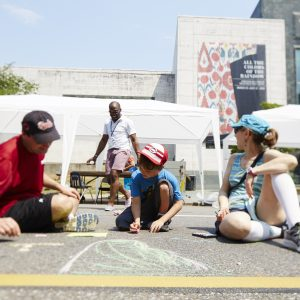 BMA staff draw a map of the Caribbean with chalk on 8th Avenue.