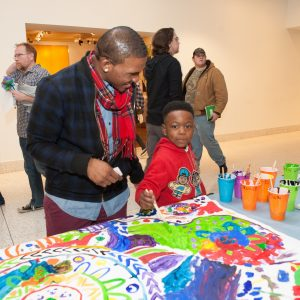 Father helping son at the painting art activity station.