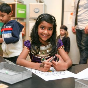 Young girl smiling in Bart's ArtVenture as she colors on a Holi Festival activity sheet.