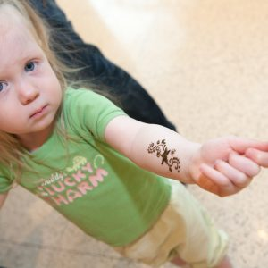 Young girl showing her henna art on her arm during the Holi festival.