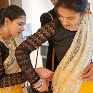 Dancer helping friend with costume before performance at the Holi Festival.