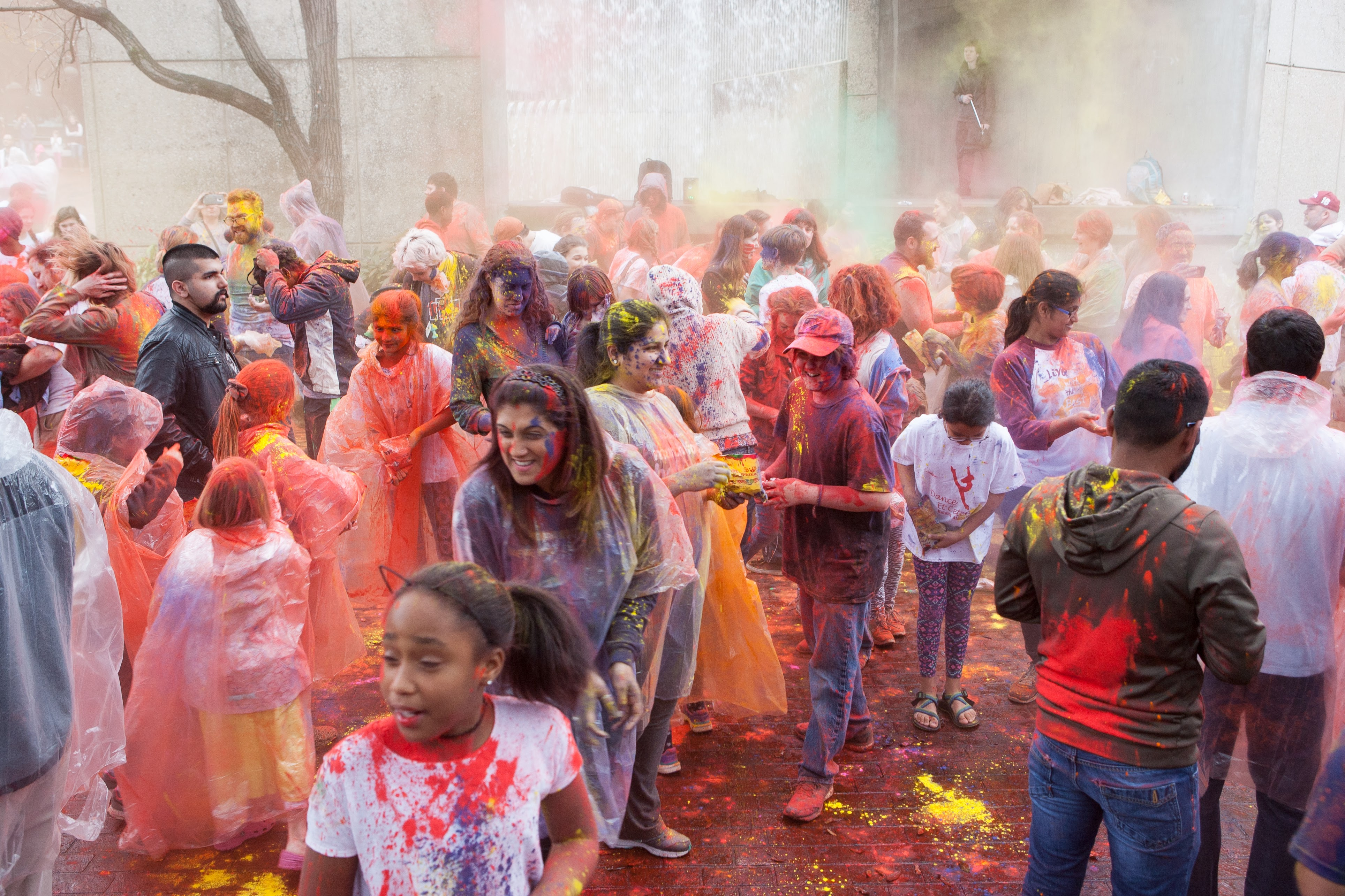 People throwing colored powders on the garden walk during the Holi Family Festival.