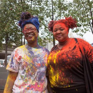 Two women stop to show off their color powder covered clothes during Holi Festival.