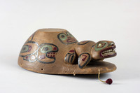 Made of red cedar shaped like a cap with a bill. The bill has thirteen bead and red yarn pendants. Above the bill is a sea lion with abalone eyes and bone teeth. A face and two killer whales are painted on the crown. The top is flattened for the attachment of cylinders of basketry which part is missing. The paint is black dark red and blue-green.