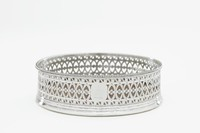 Circular, silver wine coaster, or bottle slider, with a turned walnut base, the sides pierced with at top and bottom a band of wave scroll motif, the central band a modified guilloche pattern, with a square plaque with truncated corners that once held a crest, the upper edge beaded.