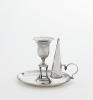 Simple, small silver chamber candlestick with attached snuffer, the well round with beaded edge, the edge of the C-scroll handle/snuffer holder likewise beaded, the urn-shaped candleholder raised on an open pedestal that would have held a fire starter or match, the upper flared rim of the candleholder likewise with beaded edge and the foot decorated with bright-cut engraving, the conical snuffer fits into the holder with an L-shaped hook and has a beaded edge.