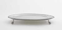 Simple, plain, round silver salver resting on four ball and claw feet, the rim beaded.