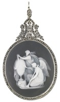 Small oval medallion of white jasper with black dip and white bas relief of Fame Inscribing an Urn to the Memory of Elisabeth, Archduchess of Austria (1767-1790) – a winged Fame kneels before a large urn on pedestal with trumpet in left hand and stylus in right, he inscribes the urn while a standing classically-dressed figure behind him drapes it, the Austrian eagle lies at the base of the pedestal, the scene delicately shaded with black jasper slip, set in a silver mount adorned with marcasite, the elaborate finial comprised of flowers and leafy elements set with marcasite, with eye for a chain.