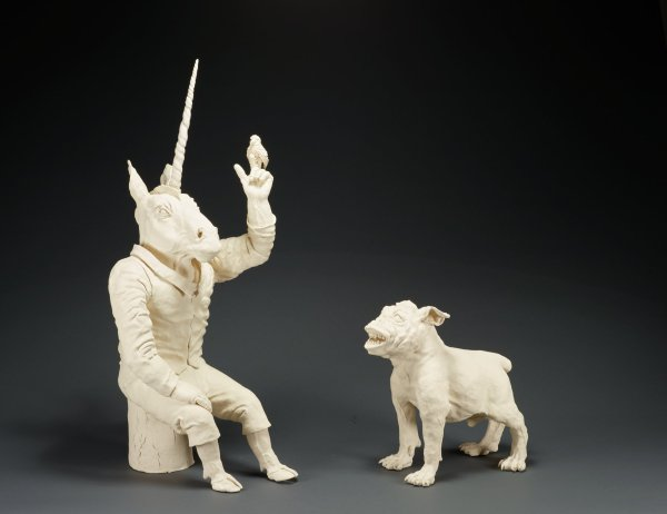 Two piece sculpture with a unicorn seated on a stump and a bulldog.