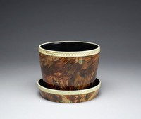 Flower pot and corresponding underdish of white stoneware covered with a variegated agate glaze in shades of brown, black, creamy yellow and green, both the pot and the under dish have a basket weave border below the lip, left white, the interiors are glazed black.