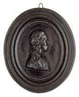 """Portrait bust of Friedrich von Schiller in profile right in """"artist's"""" garb - an open, ruffled collar and cloak with wide lapels - his hair drawn back in a """"queue"""" or ponytail, in an attached, molded cast-iron frame."""
