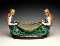 Large centerpiece of Wedgwood majolica in the form of two naiads, or nymphs, each with long brownish-blond hair held back by a leafy wreath encircling their heads and wearing a blue bathing costume, amongst molded, blue-green waves that form the base and holding between them an outstretched fishing net that serves as a basket for fruit or the like.