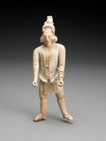 Standing male figure with legs spread, arms held slightly forward, hands cupped toward thumbs. Figure wears headdress with raised knobs, earspools, tunic, belt with front and back flaps, bracelets, sandals. Facial features include high forehead, downward-gazing eyes, classic prominent nose-bridge, slightly open mouth.
