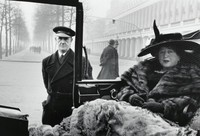 On the right, a woman in a hat, fur coat, and gloves is seated in a vehicle. Her driver stands on the left.