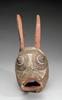 Face mask with rabbit features. Narrow vertical oval ears painted red with white interiors; protruding conical black eyes surrounded by concentric black rings with white pigment in-between; protruding open triangular mouth/snout, painted black, adorned with small incised triangles painted white and red.  Oval perimeter of back of mask pierced with multiple holes to enable attachment of mask to dancer's head as well as attachment of fiber costume.