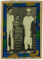 Photogragh of two black men dressed in white and two black women dressed in striped dresses.