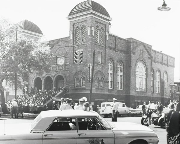 This black and white photograph represents the facade of a large brick building (Birmingham's Sixteenth Street Baptist Church) with two towers and a large street-facing staircase. The image is taken from across a street corner. The staircase of the building is covered in a crowd of African American people, and on the surrounding streets there are a number of white police offiers and police vehicles, including one that dominates the lower edge of the image. A tree stands in front of part of the building's facade and a street light floats in the upper right corner of the image.