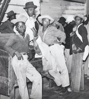 This black-and-white photograph shows several black men leaning against and sitting atop a wooden bench.