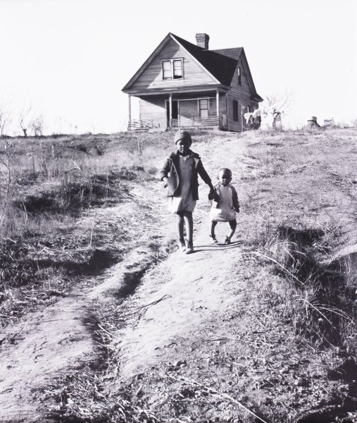 This black-and-white photograph shows two children walking down an eroded hillside away from a house and toward the camera. The elder child wears a hat and coat; the younger child has bowed legs, a sign of rickets.