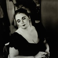 Black and white image of the actress Lola Pashalinski with her eyes closed, about to apply makeup.