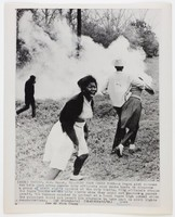 """Press print with caption """"CAMDEN, ALA. March. 31--RUNS FROM SMOKE BOMB--A Negro girl screams for help just after Camden city officials used smoke bombs to disperse a group of civil rights marches at the city limits. City officials stopped the Negro youths at the city limits when they could not produce a parade permit. The Negroes marched to protest at a local Negro high school which the principal would not permit his students to take part in civil rights demonstrations. (AP Wirephoto) (bh41900sft/bh)  1965 / See AP Wire Story"""""""