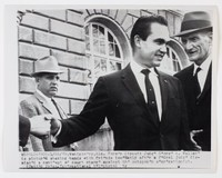 Black and white press print of a white man (George Wallace) shaking hands with someone out of view of the camera while speaking to a man on the right. Another suited man looks on from behind.