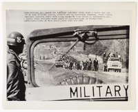 "Press print with caption ""(SEX-15) SELMA, ALA., MARCH 22- MARCHERS CONTINUE THEIR HIKE - Under the eye of an Army military police, ordered out by President Johnson, civil rights marchers continue their walk along Route 80 from Selma to Montgomery, Ala. today. Other soliders stand guard at intersections in backgound. (APWirephoto) (See AP Wire Story) wfa2 1315 stf/1965"""