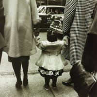 A rear view of two black women holding hands and walking down the street with a black child. The women and the child don dresses and overcoats. The heads and shoulders of the women are not visible due to cropping at the top, and the purse held by another cropped figure creates a dynamic diagonal at the bottom right.