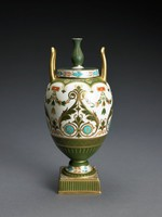"Vase of bone china in the shape of the First Day's Vase with bulbous body and small foot resting on a small square plinth, with two upright, elongated handles, the flat cover with baluster finial, the vase in the ""Aesthetic style"" and elaborately decorated on a white ground with two large inward curling scrolls on all four sides in shades of matte olive green, turquoise, and gold, in between are leafy swags extending from orange and gold rectangular reserves above a stylized acanthus leaf element, the lower body in matte olive green with cross hatching and parallel lines in gold, the shoulder of the vase with gold anthemion motifs against a matte olive green ground, the handles gold and the foot decorated with a band of leafy elements in orange and turquoise, a similar band runs around the side of the cover, the top of the cover and the finial in matte olive green highlighted in gold, the square base matte green on the sides and likewise highlighted in gold."