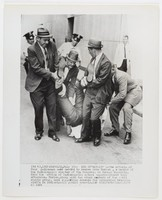"Black and white press print of an African-American civil rights activist being carried by four policemen while three others watch from behind.  Includes caption ""(NA 4), INDIANAPOLIS, July 30-- END OF ""SIT-IN"" --The efforts of four policemen were needed to remove John Torian, a member of the Indianapolis chapter of the Congress on Racial Equality, from the office of Indianapolis school superintendent this afternoon. Torian, along with two other members of the civil rights group, were supporting demands for integrated teaching staffs in Indianapolis public schools. (AP WIREPHOTO) (bd51629-n) 1964"""