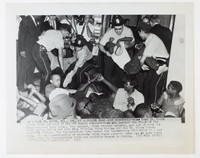 """Black and white press print of police breaking up a group of African American protestors during the middle of a sit-in. Includes caption """"SW 1 EAST ST. LOUIS, ILL., AUG. 15--POLICE DRAG AWAY DEMONSTRATORS** East St. Louis police carry out some of the 170 racial demonstrators who covered the floor of the First National Bank today. The protest, which started quietly, got out of hand and local police called for help from Illinois State Police and the St. Clair County Sheriff's Office. The demonstrators were booked for assembling unlawfully in a mob form. It was a continuation of protests which began several weeks ago at some local banks, which the demonstrators claim are racially biased in hiring. (SEE WIRE STORY) (AP WIREPHOTO) (tp51555P-D) 1963"""""""