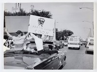 Black and white press print of a young, white male holding a protest sign while riding in a convertible on a crowed street. Three other men are in the car with him. Photograph is from the Sun Times, labeled as Gage Park Area.