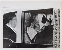 "Black and white press print of two men covering their faces in the backseat of an automobile. Cropped very close. Includes caption ""(BM1) BIRMINGHAM, Sept. 30 (AP)-Two unidentified men with part of their faces showing despite cover-up attempts arrive at city jail here last night as they were being questioned in connection with recent bombings in Birmingham. (AP Wirephoto)"""
