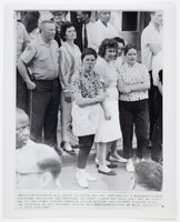 """Black and white press print of a white woman (center) sticking her tongue out at civil rights marchers. She is part of a crowd gathered on a sidewalk to watch the marchers in front of them (partially pictured). Includes caption """"Montgomery, Ala. March 25--THOSE ARE HER SENTIMENTS--A Montgomery, Ala. spectator expresses her feelings as civil rights marchers pass her on their way to the state capitol today. A police officer and several negroes stand on sidewalk as the marchers strode by. (AP Wirephoto)"""""""