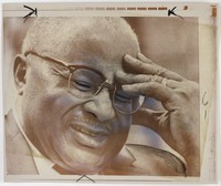 Black and white press print of an older African-American man with his head in his hand and his eyes closed. Cropped very close.