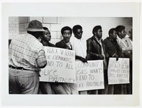 Black and white press print featuring a group of African-American men lined up against a brick wall and holding various white protest posters.