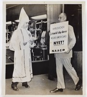 """Black and white press print showing two white men on a city sidewalk, one dress in KKK regalia and another in a suit holding a white protest poster that reads, """"KHRUSCHEV could stay here NEGRO AMERICANS NYET! NAACP""""."""