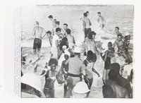 """Black and white press print of a large mixed crowd of young adult swimmers wading in the ocean. One white police officer stands in the midst of the crowd while the white helmets of two more officers can be seen in the foreground. Includes caption """"(STA8) ST. AUGUSTINE, FLA., June 20--WHITE AND NEGRO BATHERS BATTLE--Helmeted policemen wade into the surf to try and break up a battle which started after a group of integrationists entered the segregated beach. (APWirephoto) (jk71840stf) 1964"""""""