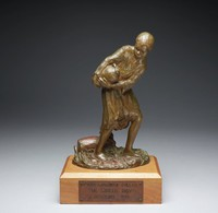 This bronze sculpture represents a young black boy carrying a small-mouthed jug. Both of his hands are wrapped around the jug in his arms, and another jug lays on its side at his feet. He is clothed in a tunic-like garment, and his posture is active: swinging arms, a cocked head, and bent knees.