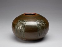 The vase is heavy. The vase's form is rotund and its exterior resembles a sea urchin, with five vertical bands comprised of six columns that contain impressions of circles. The exterior is glazed and a dark khaki color with some tan at the bottom of the vase. There are some color inconsistencies in the pattern along the vase, with some tan or green areas. Along the bottom of the vase are indentations of circles of varying shapes, interspersed with no discernible pattern. Around the lip and bottom of the vase are thin, orange rings. The interior of the vase's lip and the bottom of its base are unglazed red stoneware. The vase's interior is lighter in color and greener than the exterior.