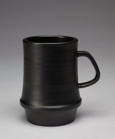 Mug with a cylindrical form and ravenstone glaze. The form flares at the bottom of the mug and tapers towards the base. The exterior is decorated with plain, dimensional bands most likely formed during the shaping process. These bands do not continue past the flaring of the form and the bottom part of the mug is smooth. The mug's handle is a rounded square, placed at an angle to the mug. The mug's interior is also uniformly glazed.