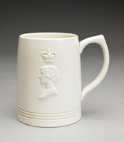 Large cylindrical creamware mug with pointed loop handle, shape number 3810 by Keith Murray, covered with a creamy, matte white Moonstone glaze and decorated on one side with the bas relief portrait of George VI (1895-1952; reigned from 1937) facing right below a crown and on the opposite side the portrait of Queen Elizabeth facing left below a crown.