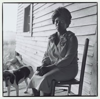 A black woman sits in a chair on a front porch with a dog.