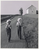Two Amish boys in white hats walk down a road toward a white building.