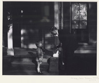 This black and white photograph shows a man and a boy outside of a residential building. The man stands on the right and bends down to hand a camera to the boy, who stands facing him at the left.