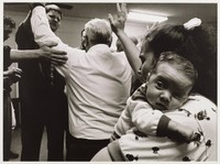 Men in a circle raise their arms in the air. A woman holding a baby is in the foreground.
