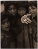 Children huddled together; one stretches out a hand on which there is a coin.