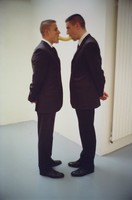 Two men in dark suits face each other and hold an unpeeled banana between them in their mouths.